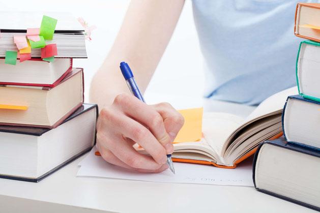 Studentin notiert auf Blatt Papier zwischen Bücherstapeln