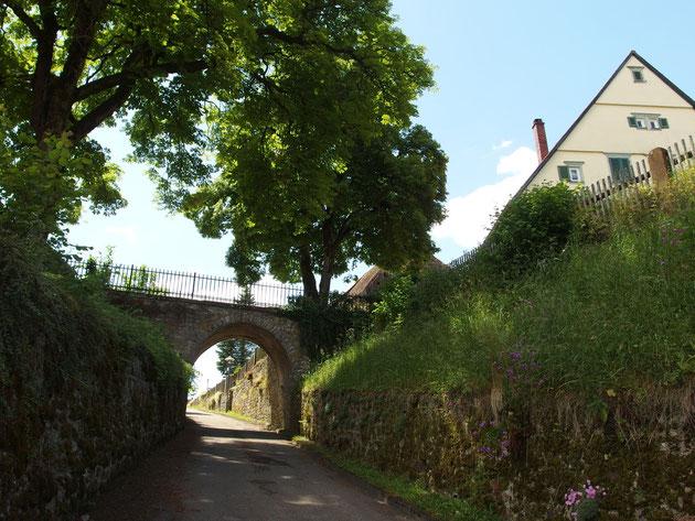 Rechts das Pfarrhaus, welches an der Stelle der ehemaligen Burg steht. Der Fußweg ist der ehem. Burggraben.