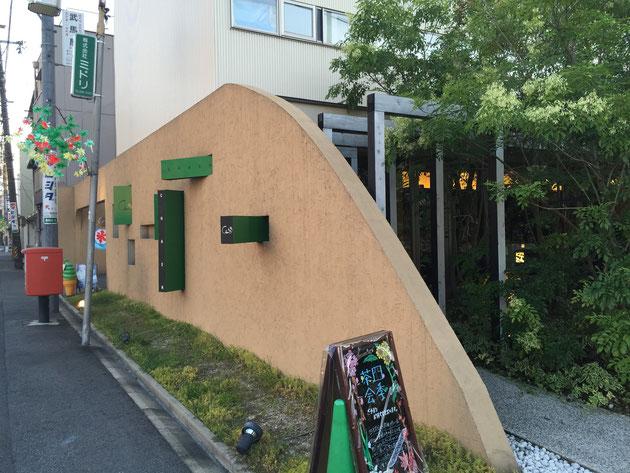 茶縁さんのファサード シマトネリコの緑と大きな壁が特徴的だ