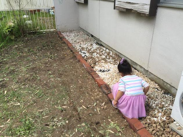土を削って防草シートを敷き土との境にレンガをしきました。
