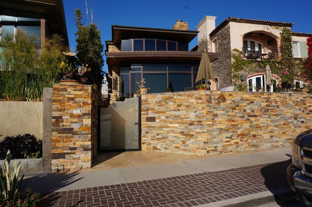 石を張ったモダンな外構もある。高台にあるため、殆どが2段土留めにしてグリーンで土留めを隠しているが、ここはあえて塀を高く存在感あるデザインで見せている。