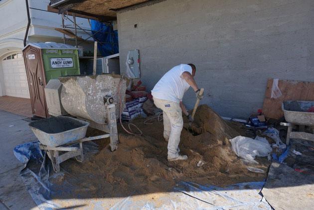 日本では馴染みのない、柄の長いスコップで広い開口部へ砂を入れていく職人さん。
