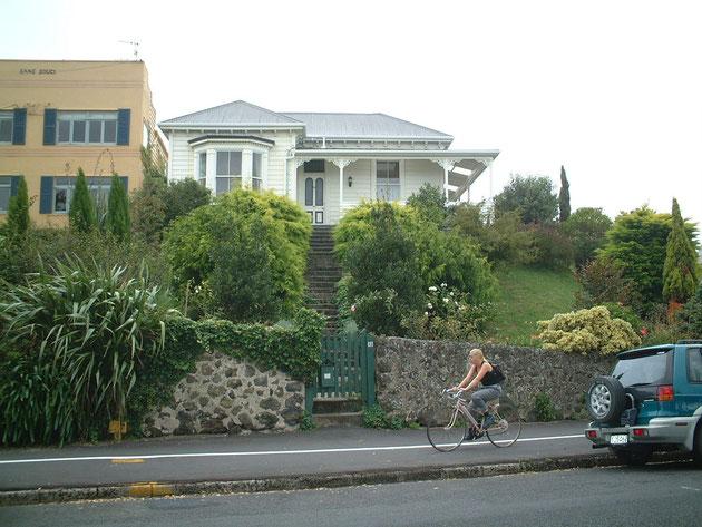 高台に建つ家 石積みの壁と奥深いグリーンがとても印象的