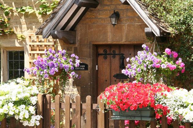 こちらの民家もあふれんばかりの花。全てハンギングでデコレーション。家を美しく飾るにはもってこいのハンギングバスケット