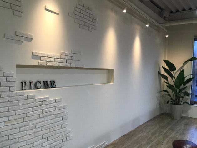 壁にはタイルが張られ、くぼみが作られた部分には素敵な素材で作られた表札が。そのまま外構で使えそう。