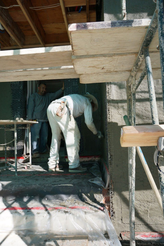 モルタルを家の外壁にに塗る職人さん 家の外壁の下地塗り