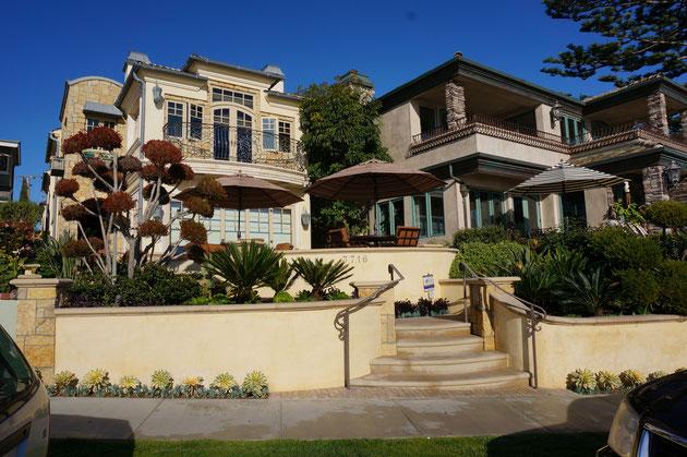 カリフォルニアっぽい色の土留めと植栽。その奥にパラソルのある庭空間が広がる。カフェできますね。
