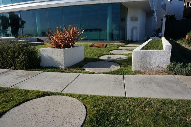 道路からのアプローチ。歩道をはさんで敷地の中にも同じスタイルのアプローチになっている。