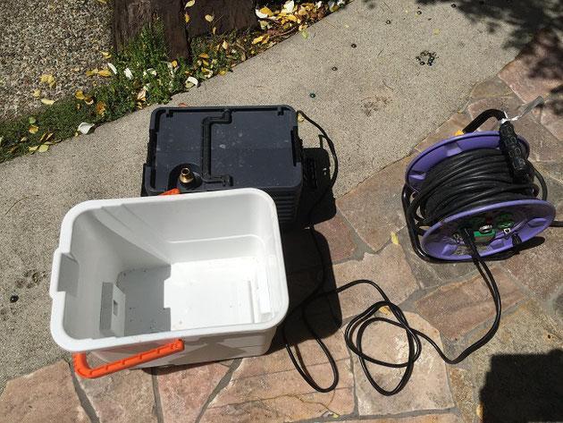 水のたまるバケツから本体を出してコードリールに繋ぐ。電気はいります。