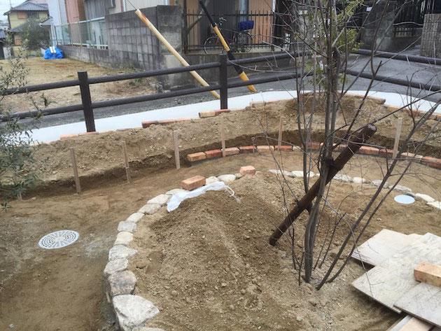 Rのレンガのラインと天然石で縁取った円形の花壇。芯はあえてずらして園路に強弱を付ける設計。