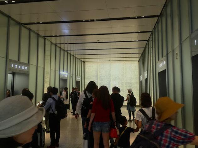 ガラスと照明で明るく演出されたJRゲートタワーのエレベーターホール。