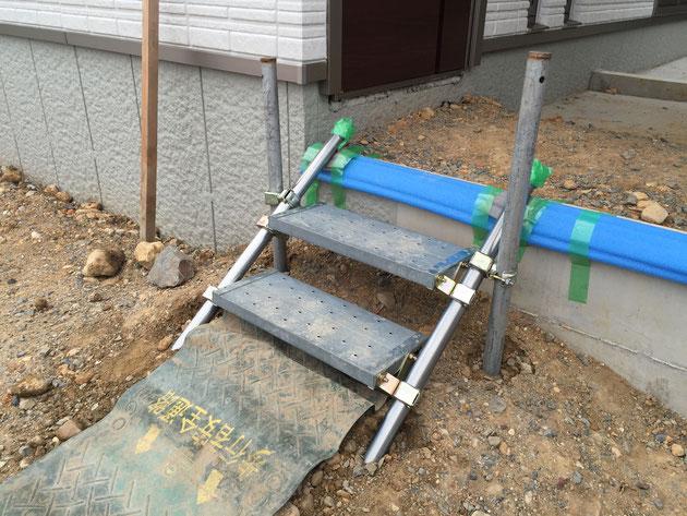階段の両サイドに単管杭を打ち込んで金具で留めて固定する。