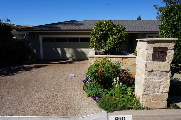 こちらの家もビルドインガレージがついている。天然石の門柱と柑橘類の植木がカリフォルニア!