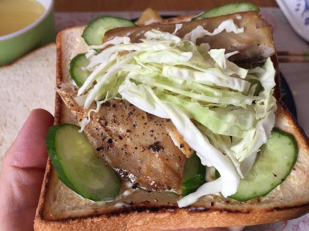 キュウリ、サバの薫製、キャベツをパンの上にのせる