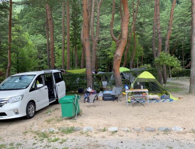 奥飛騨温泉郷オートキャンプ場の石で仕切られたキャンプエリアと隣の駐車スペース