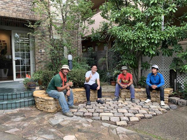 2019年9月。完成したドライストーンウオーリングの石積みの上に座る柴ちゃんと神谷造園さん!!!