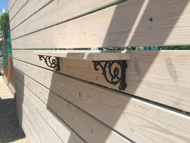 After 木製フェンスに設けた花台を支えるアイアンのオーナメント