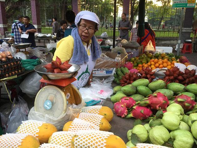 フルーツを売っているおばちゃん。はかりにのっているフルーツは何?