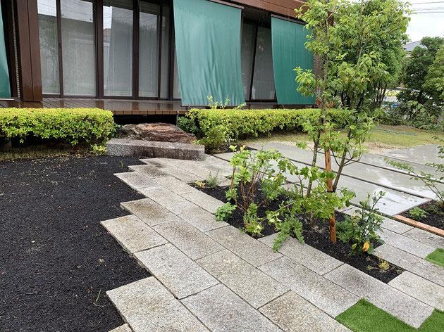 既存の御影敷石を家と家の間に敷き直して空間をつなげる通路に。