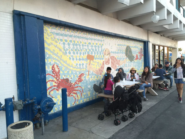 桟橋の店舗の壁に描かれたモザイク画 シェフが蟹を捕りに出かける