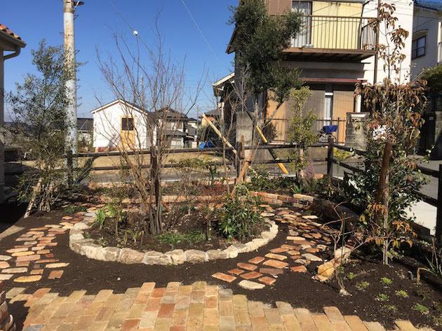レンガのR縁取り花壇と中心にもうけられた美濃石のゴロタで作られた花壇。