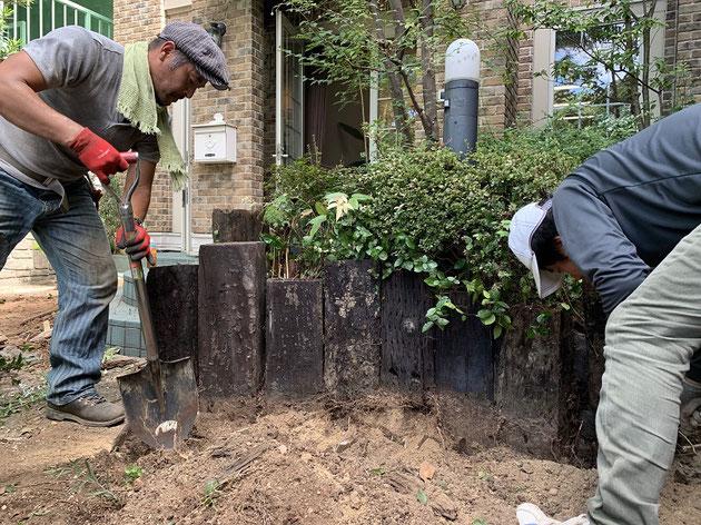 柴垣グリーンテックの事務所の枕木花壇を撤去する神谷さん