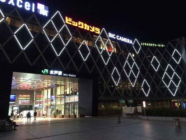 水戸駅の南口から見た夜の駅ビル。ひし形の一部が光って昼間とは違う見え方になっている。