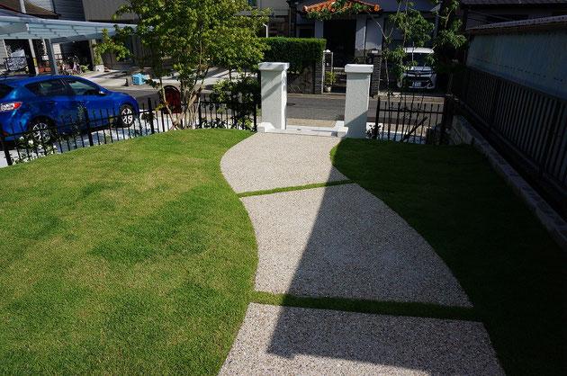 もんから伸びるアプローチは洗い出しコンクリート仕上。Rが美しい曲線を描きます。
