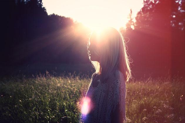 Junge Frau auf Wiese im Sonnenlicht