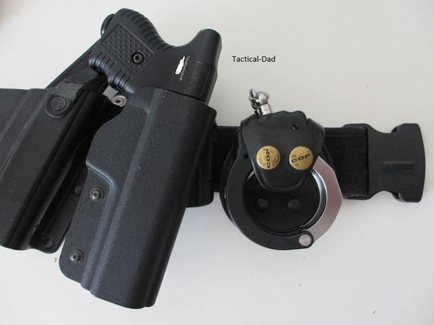 JPX mit Holster am Einsatzgürtel, zusammen mit ASP-Handfesseln.