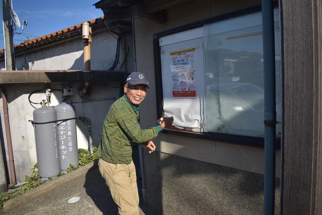 シルバーフェスタのチラシを掲示板に貼る山﨑英機さん
