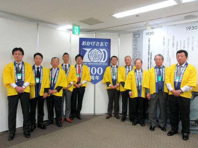 100周年ロゴ前で全役員記念写真
