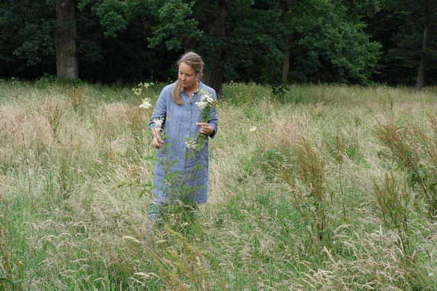 Frau steht auf einer Wiese und pflückt Blumen