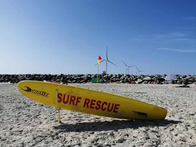 Surfbrett am Strand auf dem in rot Surf Rescue steht