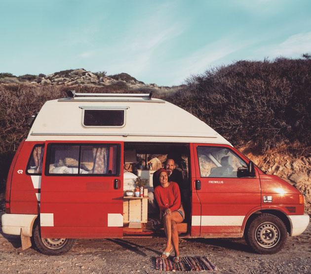 Ein Mann und eine Frau sitzen bei offener Tür in einem VW Bus in der Sonne