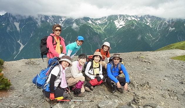 蝶ケ岳山頂で、山頂にガスかかる穂高、槍をバックにメンバー7人で