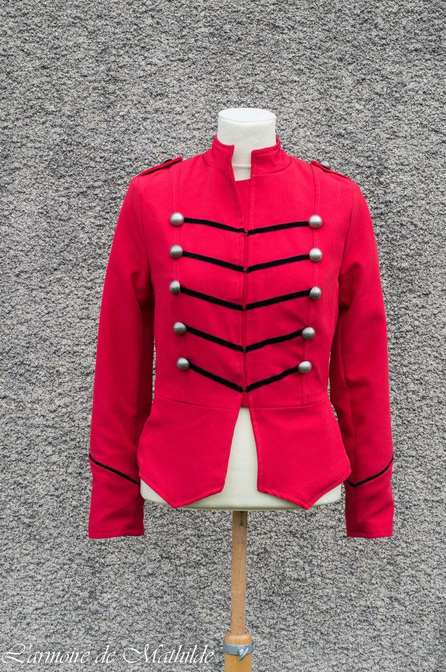 Veste en gabardine extensible rouge doublée de satin de coton noir et décorée de velours et de boutons en métal.
