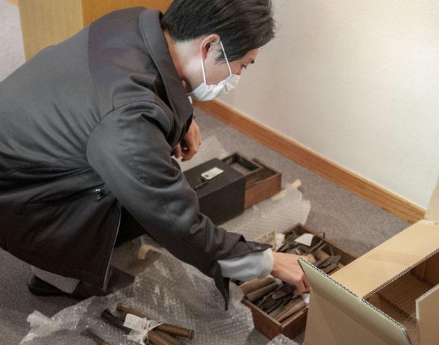 興味深く道具を調査する彫刻家で教職員の鈴木翔太さん