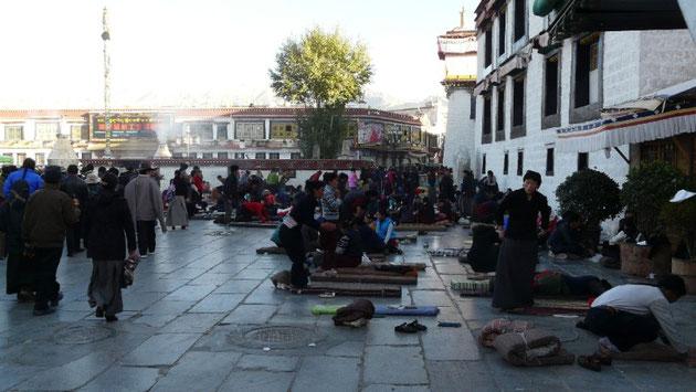 Sur la place du Barkhor, les pelerins se prosternent devant le temple