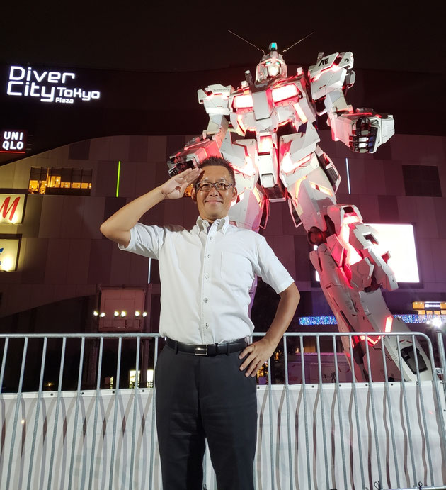 お台場に立つユニコーンガンダム前で記念撮影をする太田。