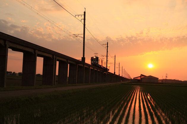 夕景 夕陽を背にくびき野を行く、間もなくくびき駅へ(ほくほく線)