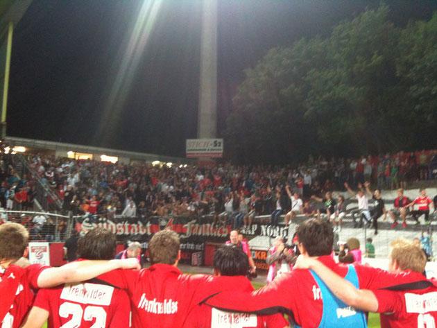 Spieler und Fans feiern nach dem Spiel gemeinsam den Sieg!