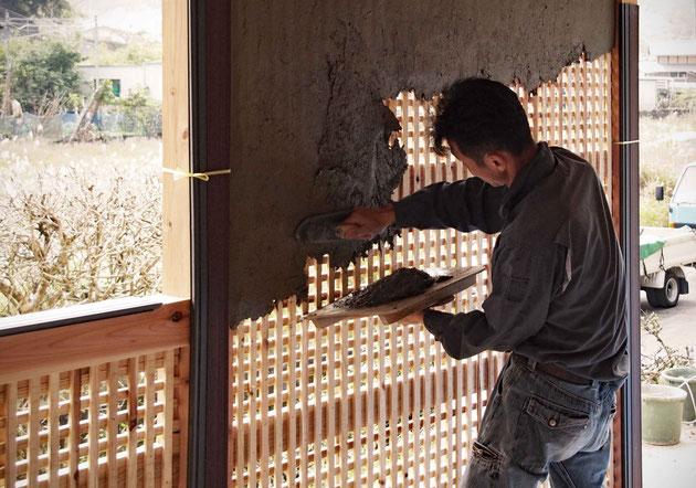 木小舞に土壁を塗っている様子