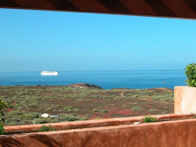 Auf dem Bild sehen Sie den Blick vom Apartment bis zum Meer, über den Küstenstreifen. Im Hintergrund am Horizont sieht man ein Fahrgastschiff.