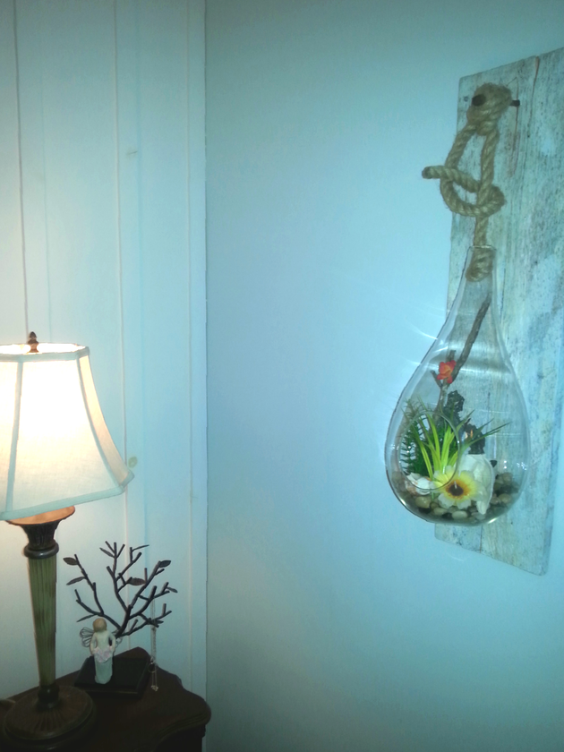 Cottage style bedroom suited this raindrop terrarium hanging from a rustic rope and spiked into a piece of barn board creating unique wall decor.