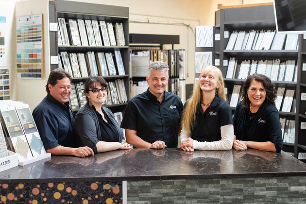 Tile Lines employees Rick, Elizabeth, and Heidi smiling for the camera in front of shelves of tile and mosaic samples.
