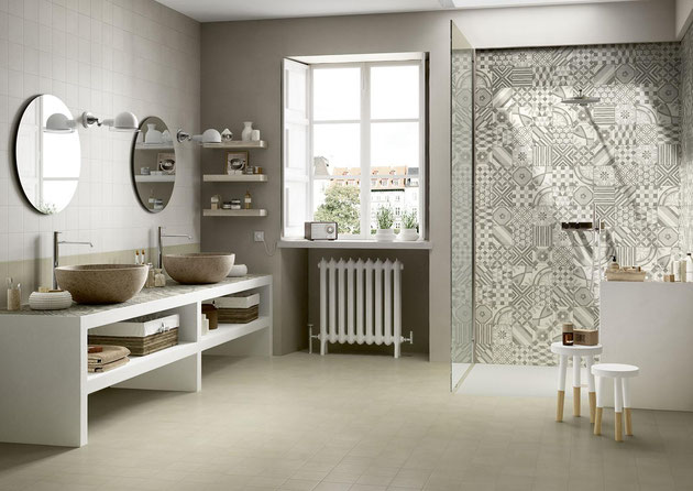 Large bathroom with a white built-in vanity with two brown vessel sinks on the left, a walk-in curbless shower with light brown patterned tiles on the wall, and a window with a white radiator underneath.