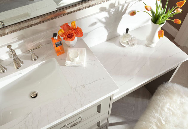 Cambria Ella white quartz countertops on a light gray cabinet with a white, rectangular undermount sink, brushed nickel faucet, a white vase with orange roses, and orange perfume bottle, and a different vase with orange tulips.