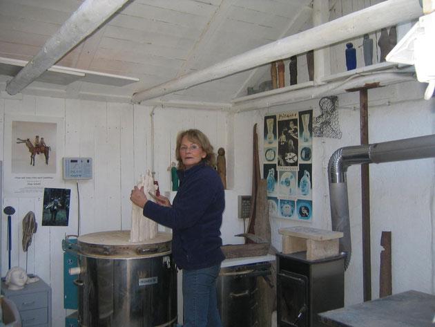 marianne schweigler in ihrem atelier, beim anfertigen einer tonskulptur. marianne schweigler steht vor ihrem brennofen