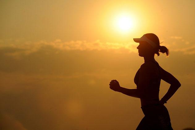 Vor einem Sonnenuntergang ist die schwarze Silouette einer Frau zu sehen, die joggt.